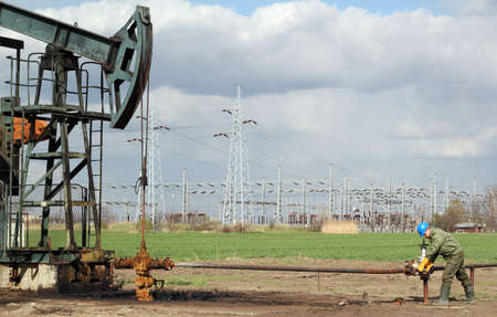 hard worker: giacimento di petrolio con pompa jack e lavoratori