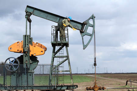 oil worker standing at pump jack photo