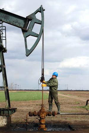 yacimiento petrolero: trabajador petrolero de pie en la tuber�a