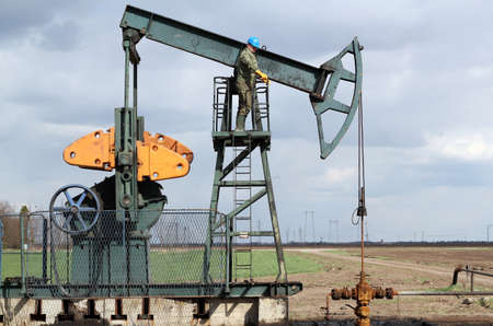oil and fuel industry oil worker standing on the pump jack photo