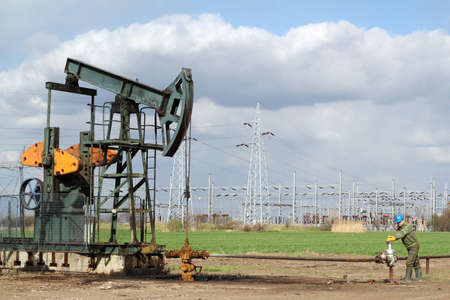 pumpjack: oil field with pumpjack and oil worker Stock Photo