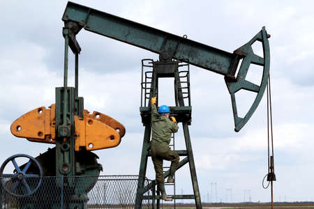 oil field: oil worker climbs to the pumpjack