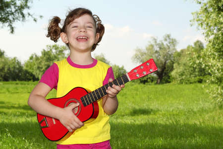 happy little girl play guitar in park Stock Photo - 14101857
