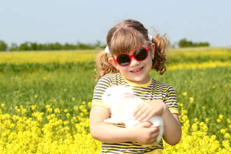 little girl with bunny pet in yellow field photo