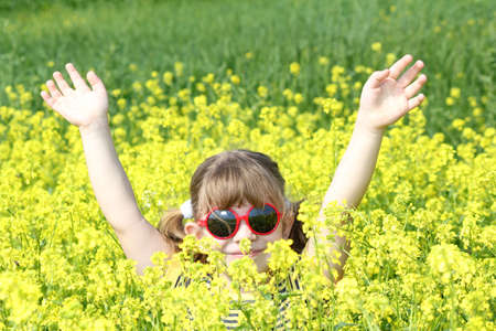 little girl with hands up in yellow flower field photo