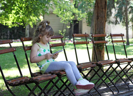 little girl with tablet sitting in park photo
