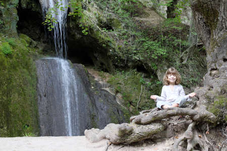 little girl meditate by the waterfall photo