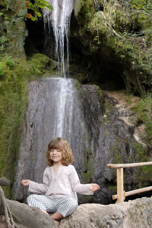 little girl meditates in nature photo
