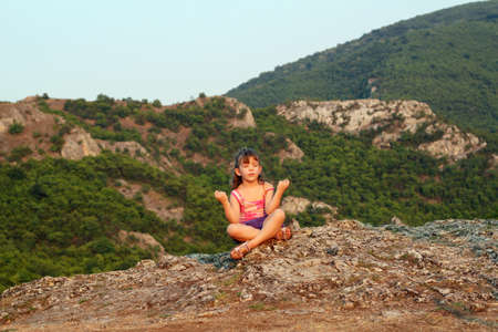 little girl sitting on a mountain top and meditate photo