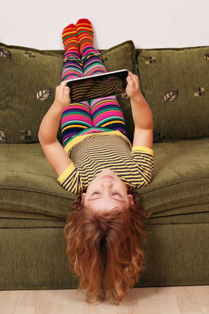 little girl lying upside down on bed and play with tablet photo