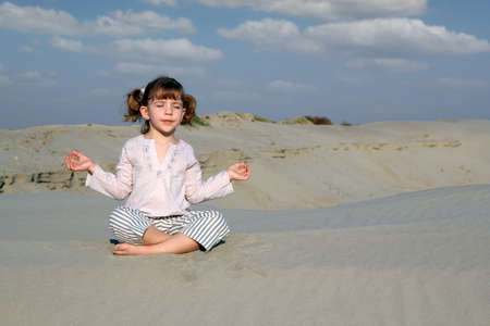 little girl meditating in desert photo