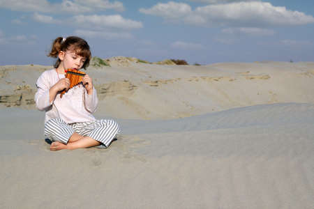 panpipe: little girl play panpipe in desert