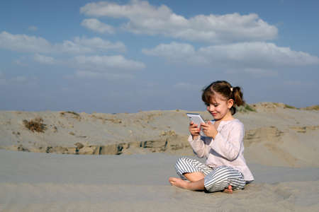 little girl play with tablet pc in desert photo