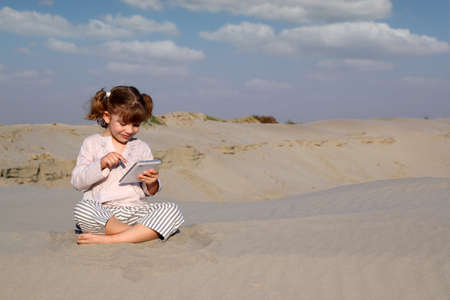 happy little girl play with tablet pc in desert photo