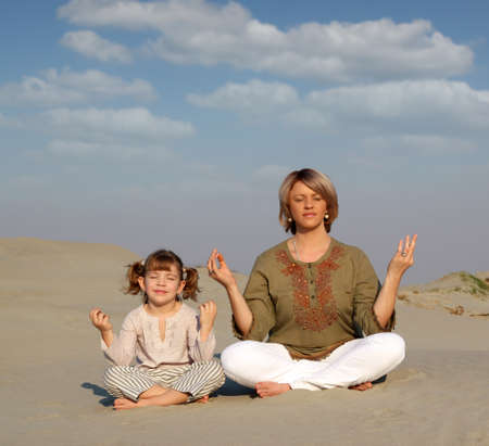 yoga meditation: mother and daughter meditating in desert Stock Photo