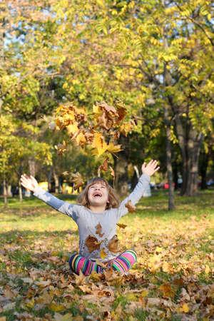young leaf: ni�a tira las hojas de oto�o Foto de archivo