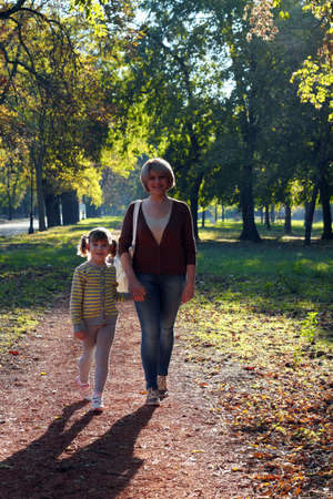 mother and daughter walking in park photo
