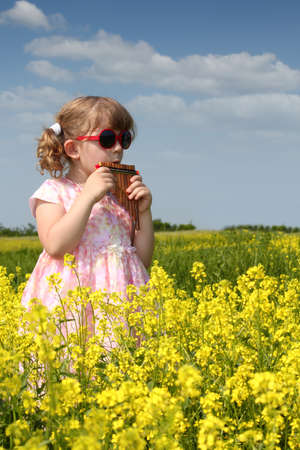 little girl standing in yellow flower field and play pan pipe