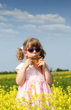 panpipe: little girl standing in yellow flower field and play pan pipe