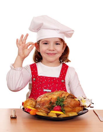 beautiful little girl cook with grilled chicken Foto de archivo
