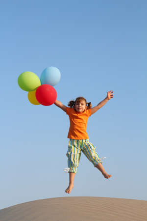 happy little girl jumping with balloons photo