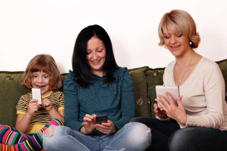 happy mother and daughters playing with smart phones and tablet Stock Photo - 17623051