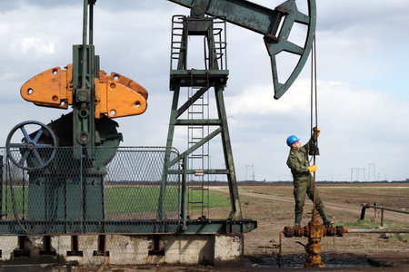 oil worker standing at pipeline and check pump jack photo
