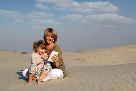 happy mother and daughter play with tablet pc in desert photo