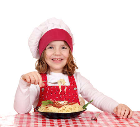 happy little girl cook eat spaghetti photo