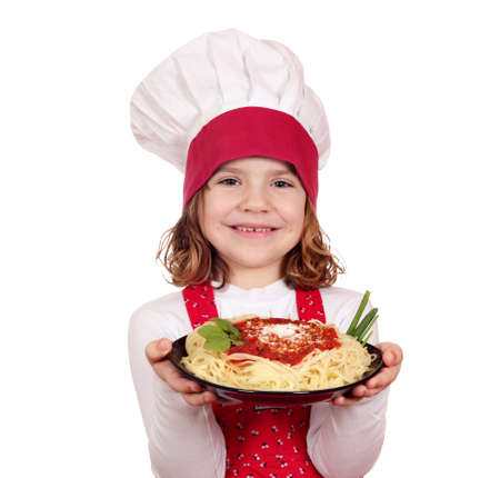happy little girl cook holding dish with spaghetti photo