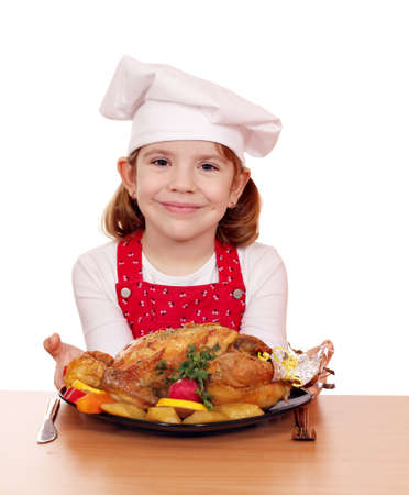 beautiful little girl cook with roasted chicken on table photo
