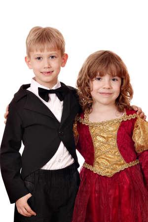 boy in tuxedo and little girl in golden red dress portrait photo
