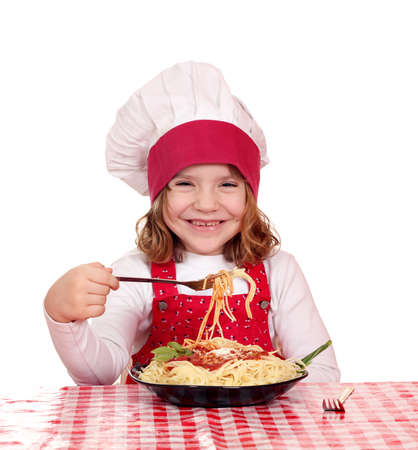 hungry little girl cook eat spaghetti photo