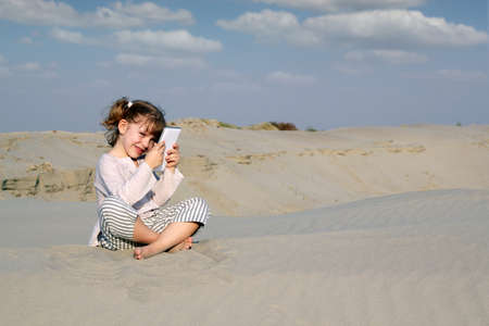 little girl sitting on sand and play with tablet pc photo