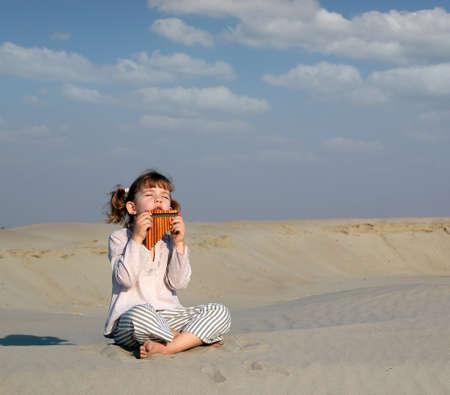 panpipe: little girl play music on pan pipe in desert