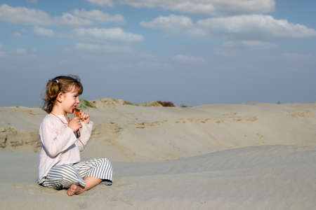 panpipe: little girl sitting on sand and play music