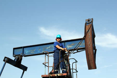 oil worker with sunglasses standing at pump jack photo