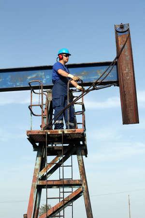 oil worker: Trabajador petrolero en uniforme azul permanente en gato de bomba