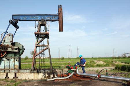 oil worker: trabajador petrolero con llave en campo petrolero