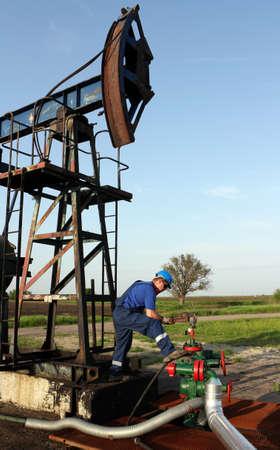 oil worker: trabajador petrolero con una llave de tubo y tuber�a Foto de archivo