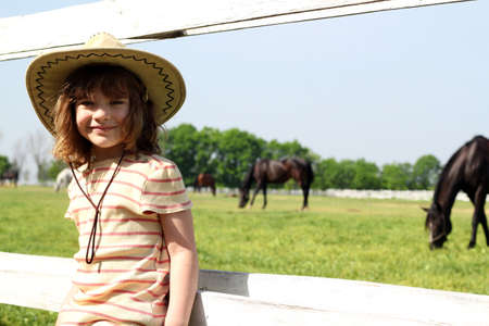 little girl with cowboy hat on farm photo
