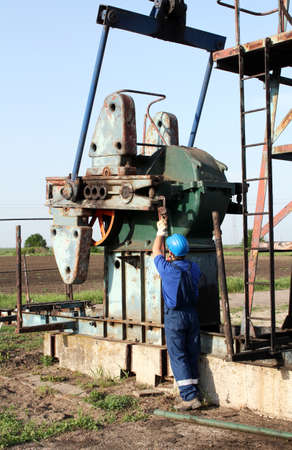 oil worker: trabajador petrolero con una llave de tubo de trabajo