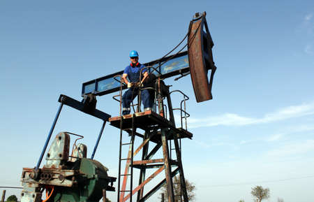 counterweight: strong oil worker standing on pump jack Stock Photo