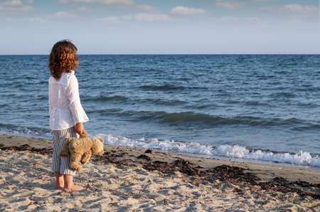 little girl with teddy bear standing on beach and looking at the sea photo