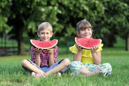 little girl and boy eat watermelon photo
