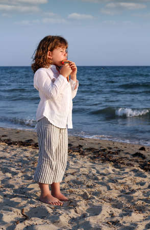 zampona: hermosa niña juego tubo de la cacerola en la playa