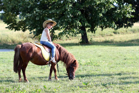 little girl riding pony horse  Stock Photo