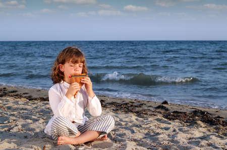panpipe: beautiful little girl sitting on beach and play pan pipe