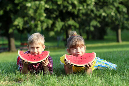happy boy and little girl with watermelon lying on grass photo
