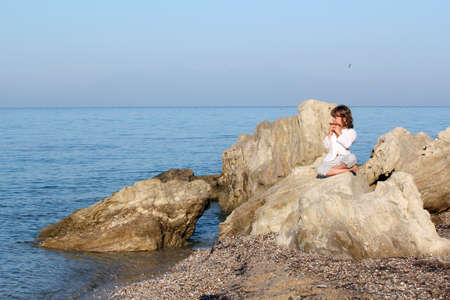 panpipe: little girl sitting on a rock by the sea and playing pan pipe